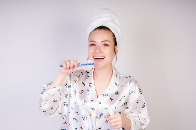 Menina sorridente com escova de dentes na manhã