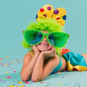 Menina sorridente com fantasia de palhaço e óculos de sol