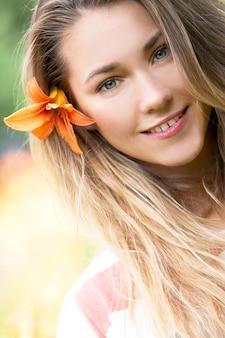 Menina sorridente com flor de lírio no cabelo