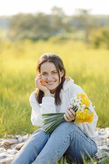 Menina sorridente com flores caminhando na floresta