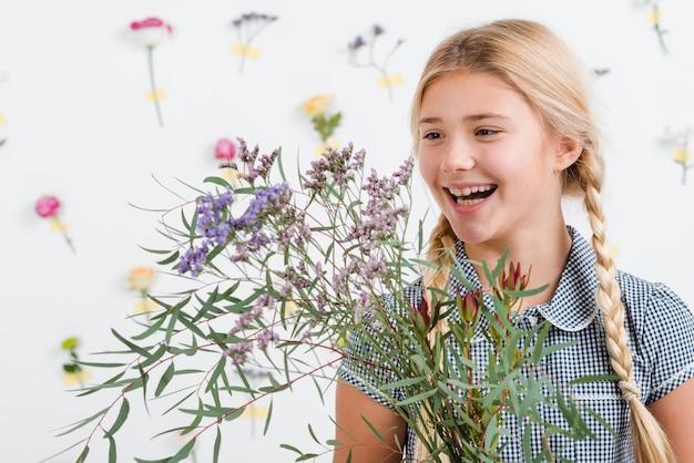 Menina sorridente com flores da primavera