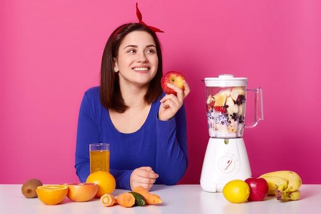 Menina sorridente com frutas frescas na mesa isolada sobre rosa