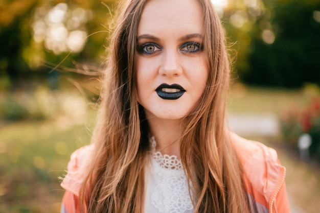Menina sorridente com gótico compõem retrato ao ar livre no parque ensolarado