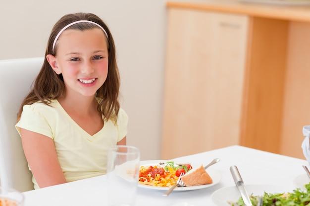 Menina sorridente com jantar na mesa