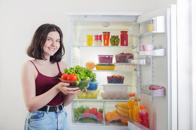 Menina sorridente com legumes perto da geladeira com alimentos saudáveis