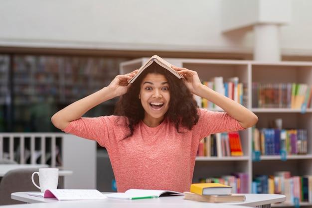Menina sorridente com livro na cabeça