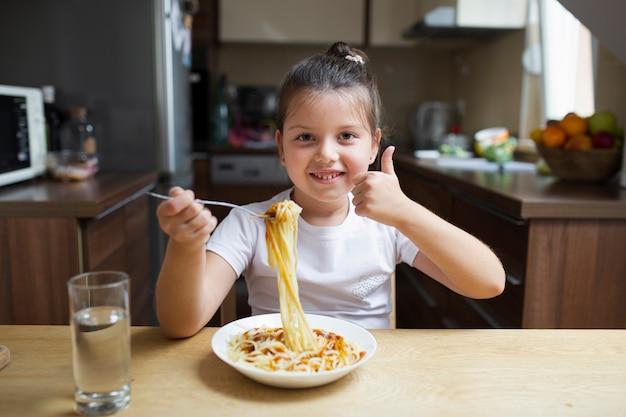 Menina sorridente com macarrão no almoço