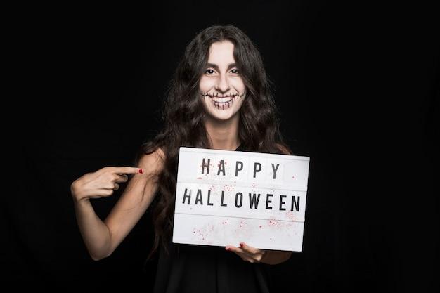 Menina sorridente com maquiagem assustadora e tabuleta