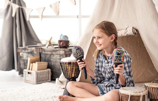 Menina sorridente com maracas nas mãos e tambores étnicos no chão do quarto infantil