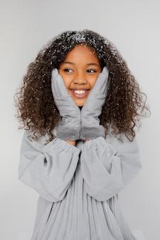 Menina sorridente com neve média tiro