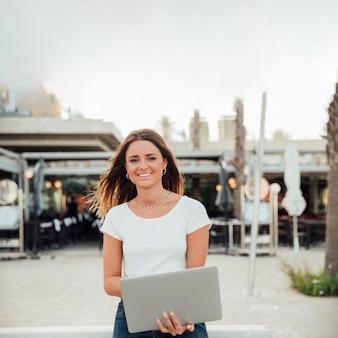 Menina sorridente com notebook, olhando para a câmera
