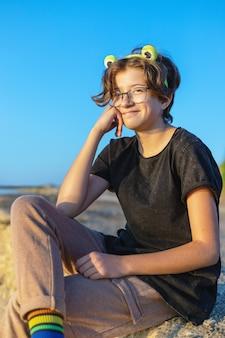 Menina sorridente com óculos com armação verde no cabelo em forma de sapo ao ar livre, tema lgbt, orgulho