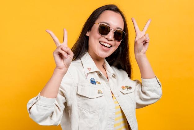 Menina sorridente com óculos de sol em fundo amarelo