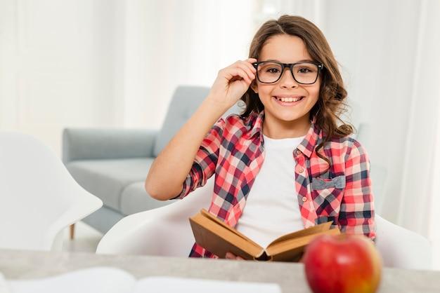 Menina sorridente com óculos em casa lendo