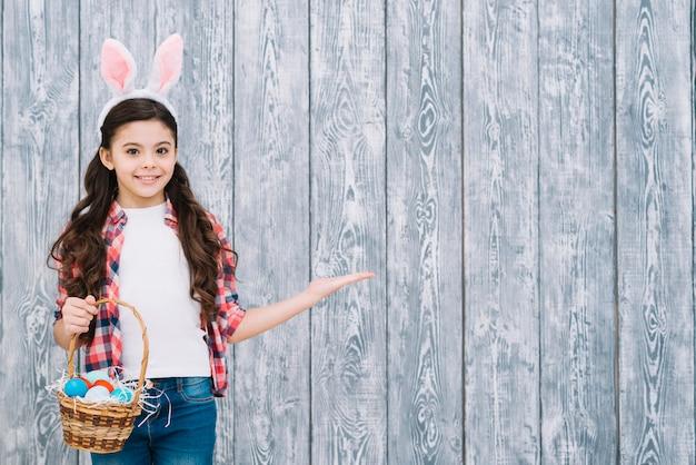 Menina sorridente, com, orelhas bunny, segurando, cesta, ovos páscoa, apresentando, contra, cinzento, escrivaninha madeira