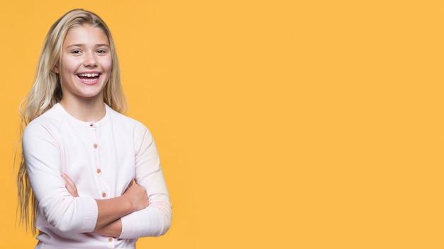 Menina sorridente com os braços cruzados em fundo amarelo