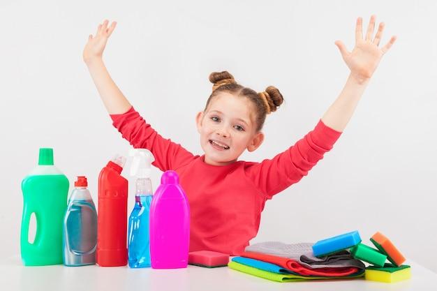 Menina sorridente com produtos de limpeza multicoloridos