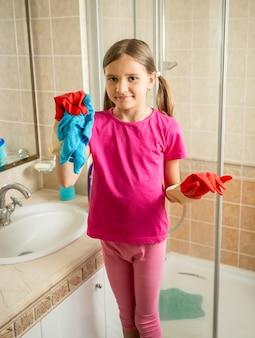 Menina sorridente com rabo de cavalo posando no banheiro enquanto faz a limpeza