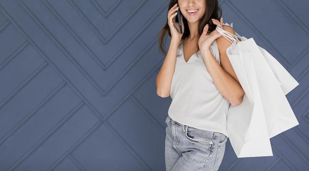 Menina sorridente com redes de compras no ombro