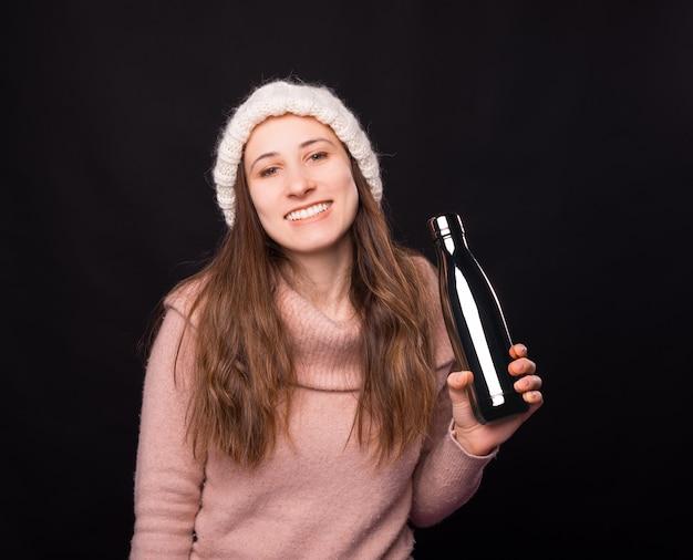 Menina sorridente com roupas de inverno está segurando uma garrafa térmica de metal.