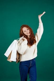 Menina sorridente com sacolas de compras em estúdio