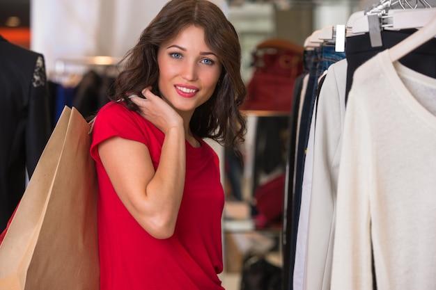 Menina sorridente com sacolas de compras na loja