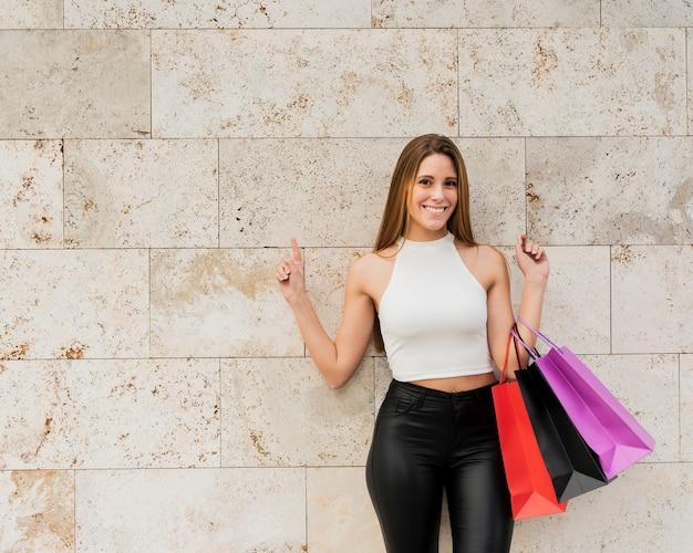 Menina sorridente com sacos de compras em pé junto à parede
