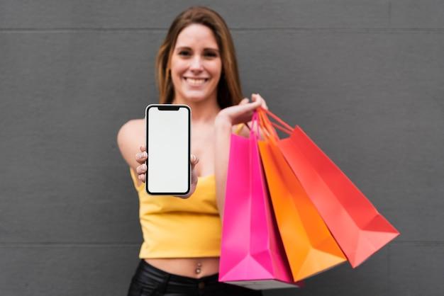 Menina sorridente com sacos de compras, segurando o telefone
