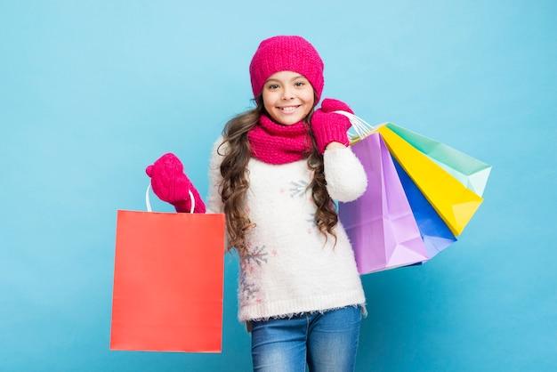 Menina sorridente com sacos de roupas de inverno