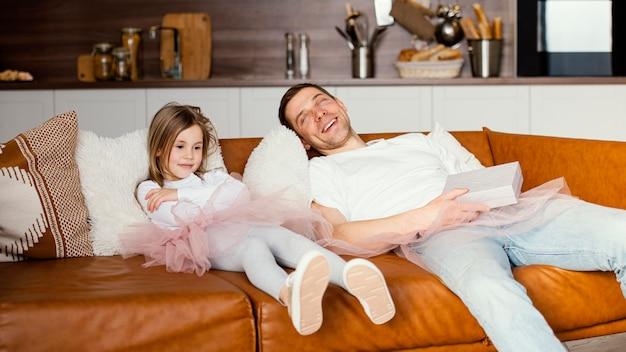 Menina sorridente com saia tutu e pai descansando no sofá