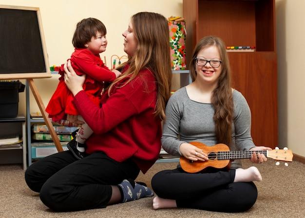 Menina sorridente com síndrome de down e mulher segurando a criança