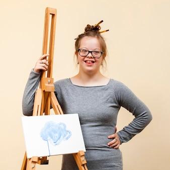 Menina sorridente com síndrome de down, posando com cavalete