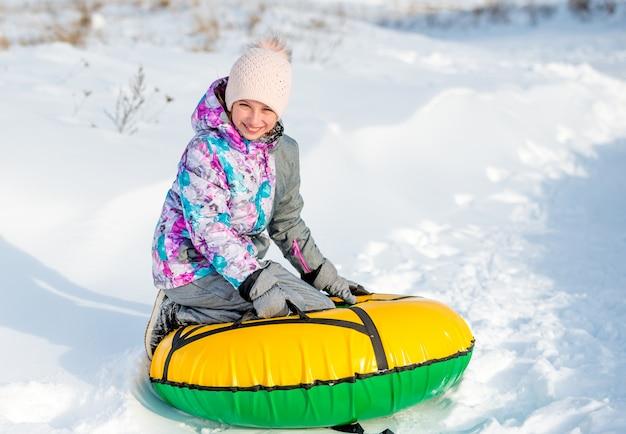 Menina sorridente com snowtube brilhante pronto para deslizar na neve