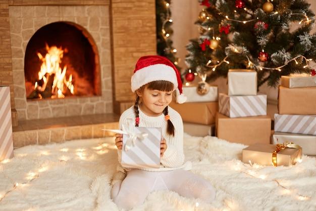 Menina sorridente com suéter branco e chapéu de papai noel, sentada no chão perto da árvore de natal, caixas de presentes e lareira, segurando um presente dos pais nas mãos.