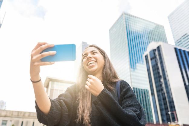 Menina sorridente com telefone inteligente em chicago