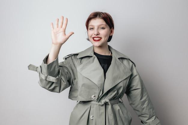 Menina sorridente com um casaco verde da moda mostrando a palma da mão