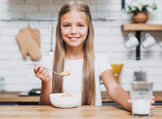 Menina sorridente com uma tigela de cereais, olhando para a câmera
