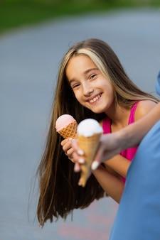Menina sorridente, comendo sorvete