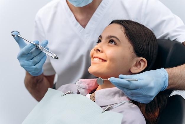 Menina sorridente confia em seu médico. o jovem paciente não tem medo de injeções, pronto para a anestesia