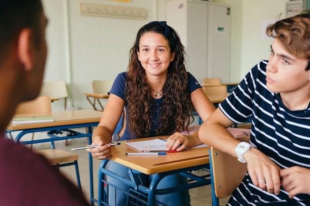 Menina sorridente conversando com meninos na aula