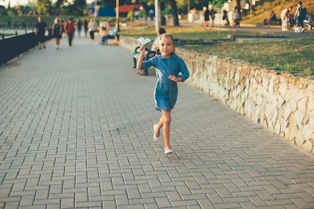 Menina sorridente, correndo com o avião de papel de brinquedo