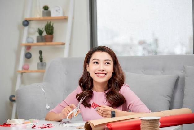 Menina sorridente cortando o coração do dia dos namorados de um papel vermelho com uma tesoura na sala de estar