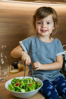 Menina sorridente cozinhando salada de vegetais verde simples.