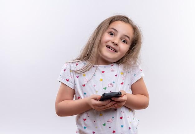 Menina sorridente da escola vestindo camiseta branca segurando o telefone no fundo branco isolado