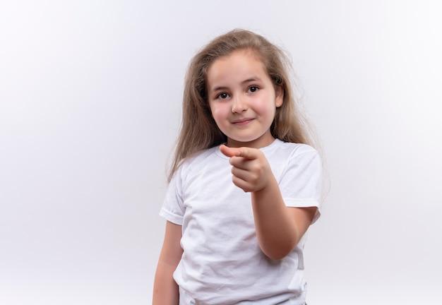 Menina sorridente da escola vestindo uma camiseta branca mostrando seu gesto em um fundo branco isolado