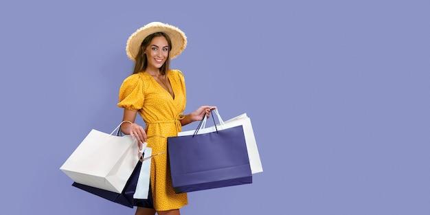 Menina sorridente da moda com pacotes depois de fazer compras em fundo roxo preto. grandes liquidações de sexta-feira