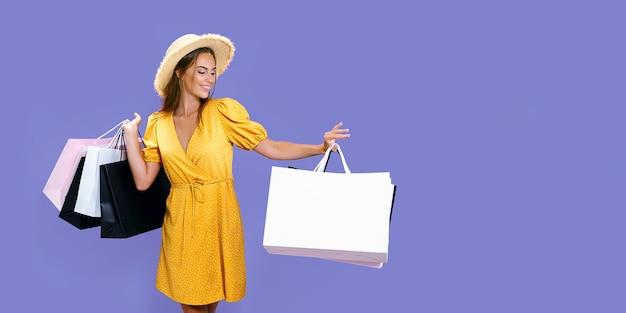 Menina sorridente da moda com pacotes depois de fazer compras na promoção de fundo lilás com desconto na venda de sexta-feira negra