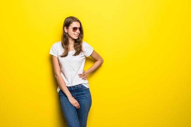 Menina sorridente da moda em camiseta branca e calça jeans azul fica na frente do fundo amarelo do estúdio