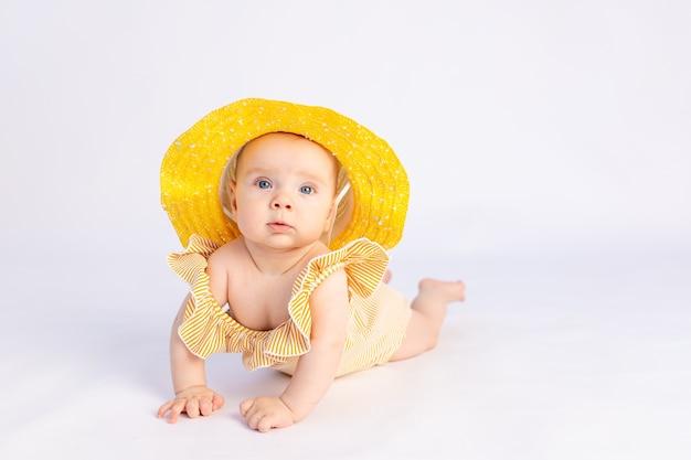 Menina sorridente de 6 meses em um maiô e chapéu de sol deitada