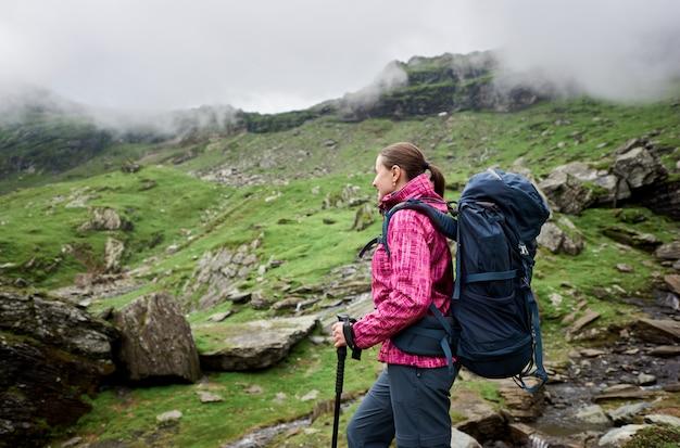 Menina sorridente de alpinista com grande mochila azul e varas de trekking andando no outono verde montanhas rochosas com nuvens de nevoeiro.